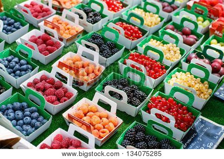 Different berries in boxes ready for selling on market in south of France, Arles, Provence. Local organic food. Raspberry, blueberry, currant