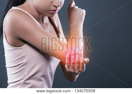 Body pain. Studio shot of beautiful young woman with dark brown hair. Woman suffering from elbow pain. Red spot on elbow