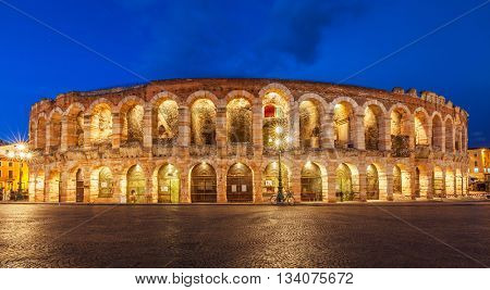 Ancient amphitheater arena di verona in italy like coliseum with nighttime illumination and evening blue sky