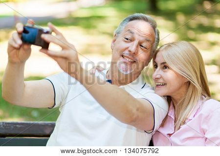 Portrait of a mature couple taking a self portrait in a park