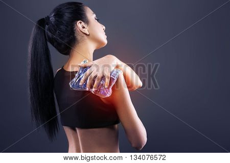 Body pain. Studio shot of beautiful young woman with dark brown hair. Woman suffering from shoulder pain. Red spot on shoulder. Woman holding freezing gel on shoulder