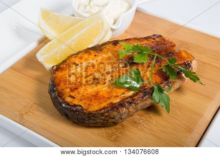 Grilled salmon stake with lemon and sauce