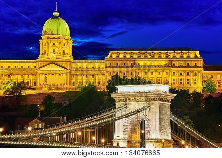 Budapest Royal Castle And Szechenyi Chain Bridge At Dusk Time From Danube River, Hungary.