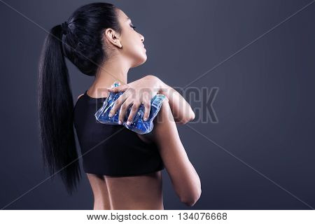 Body pain. Studio shot of beautiful young woman with dark brown hair. Woman suffering from shoulder pain. Woman holding freezing gel on shoulder