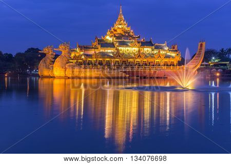 Golden Karaweik palace on Kandawgyi lake looks like an ancient royal barge. Twilight time. Yangon, Myanmar