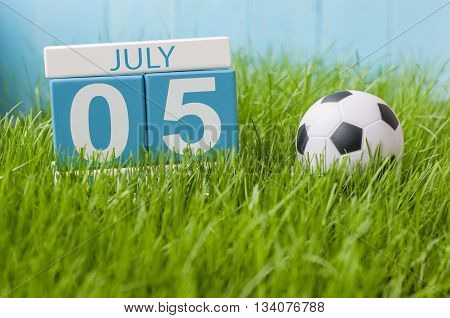 July 5th. Image of july 5 wooden color calendar on green lawn grass background. Summer day.