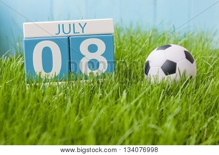 July 8th. Image of july 8 wooden color calendar on greengrass lawn background. Summer day, empty space for text.