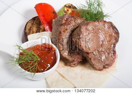 Roasted mignon steak served with vegetables and sauce
