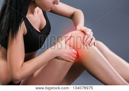Body pain. Studio shot of beautiful young woman with dark brown hair. Woman suffering from knee pain. Red spot on knee