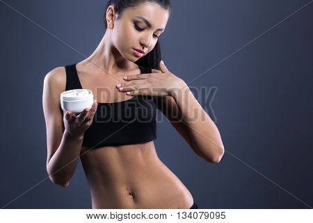 Body care. Studio shot of beautiful young woman with dark brown hair. Woman using body cream