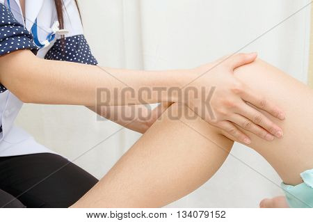 Doctor the traumatologist examines the patient's knee
