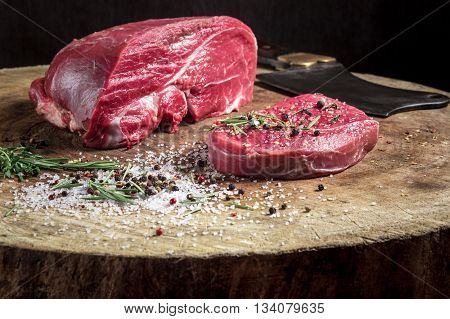 a juicy piece of meat lying on a wooden board with a butcher knife. Flavored with spices