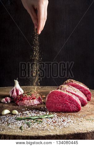 a juicy piece of meat lying on a wooden board. hand sprinkles spices