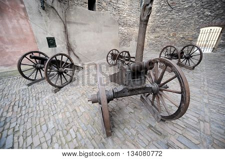 Old artillery guns in historic cobbled courtyard
