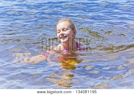 Swimming smiling cute girl seven years old