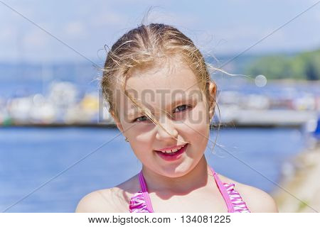 Portrait of cute girl on the riverbank in pink swimsuit