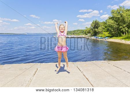 Cute jumping girl on the riverbank in pink swimsuit