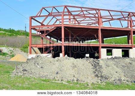 The metal frame is being built brick building and a pile of building sand
