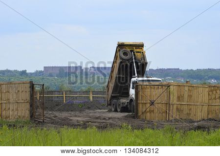 Big old tipper vith clay ground dumped soil in storage space