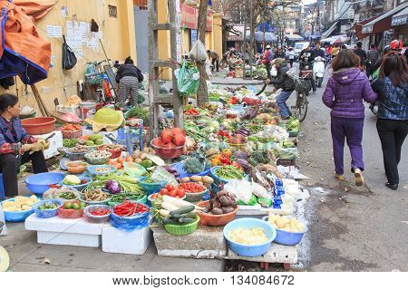 Hanoi Vietnam: February 21 2016: Womand selling fruits and vegetables in a street market of Hoàn Kiếm the old quarter of Hanoi
