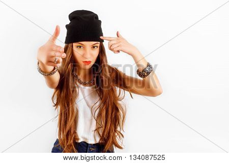 beautiful woman wearing in black hat and white T-shirt standing near white wall, shows the gun fingers of hands, fashion concept