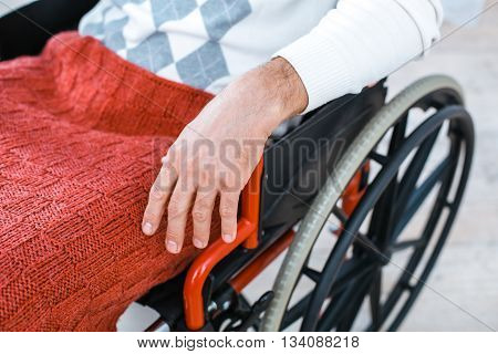 Adult man in wheelchair. Close up photo of man sitting in wheelchair