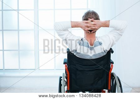 Adult man in wheelchair. White interior with big window. Man relaxing and looking at window. Back view photo