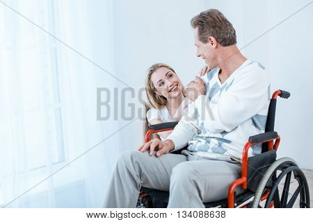 Adult man in wheelchair. White interior with big window. Man and young helper smiling