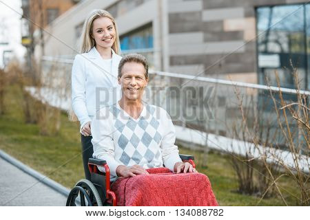 Adult man in wheelchair during walk. Man and young helper smiling and looking at camera. Nurse carrying patient on wheelchair