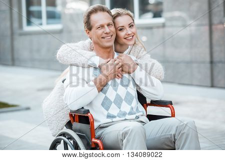Adult man in wheelchair during walk. Man and young helper hugging, smiling and looking at camera. Nurse carrying patient on wheelchair