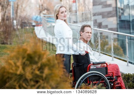 Adult man in wheelchair during walk. Young helper and man looking at camera. Nurse carrying patient on wheelchair