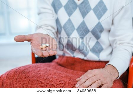 Adult man in wheelchair. Close up photo of man sitting in wheelchair and taking pills