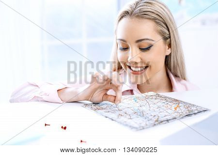 Concept for travel agent. Close up photo of young woman. Woman choosing travel destination on map. Travel agency office interior with window