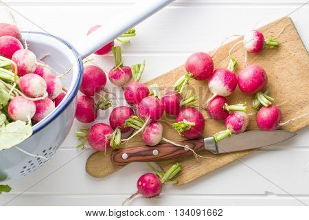 Fresh radishes on old cutting board with knife. Healthy vegetable red radishes.
