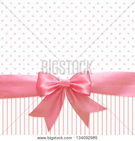 Pink silk ribbon and bow on spotted and striped background for girl