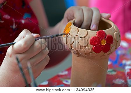 TIMISOARA ROMANIA - JUNE 1 2016: Girl who paints a ceramic bowl. Workshop organized by the City Hall Timisoara with the occasion of the International children Day.