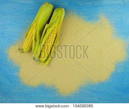 corn flour and corn on the cob on a wooden table