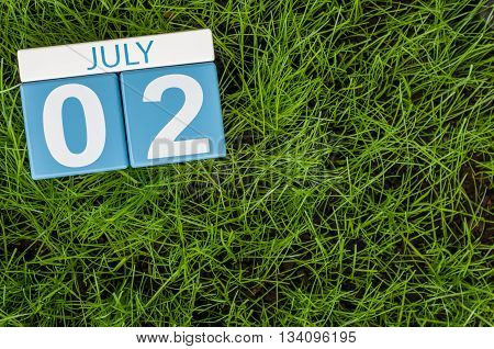 July 2nd. Image of july 2 wooden color calendar on green lawn grass background. Summer day.
