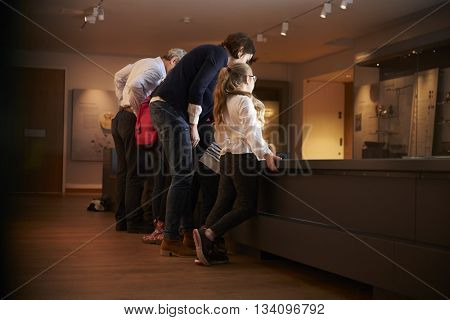 Rear View Of Pupils On School Trip To Museum Looking At Map