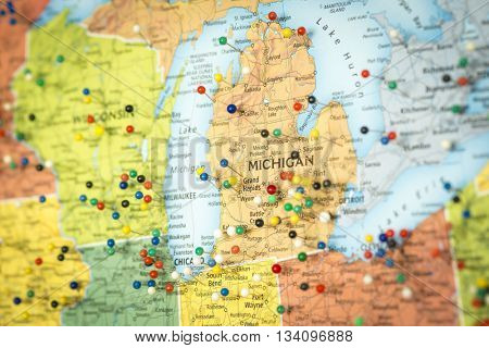 Colorful detail map macro close up with push pins marking locations throughout the United States of America MI Michigan