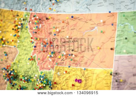 Colorful detail map macro close up with push pins marking locations throughout the United States of America MT Montana