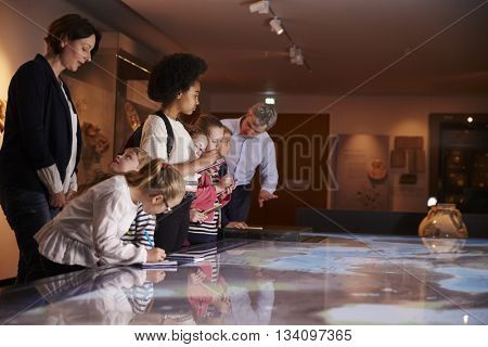 Pupils On Trip To Museum Looking At Map And Making Notes