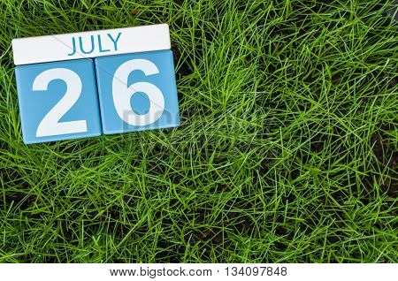 July 26th. Image of july 26 wooden color calendar on greengrass lawn background. Summer day, empty space for text.