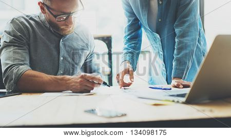 Coworkers team brainstorming process in modern loft.Project manager wearing glasses, man makes notes marker.Creative business crew working with startup studio.Laptop wood table.Blurred, film effect