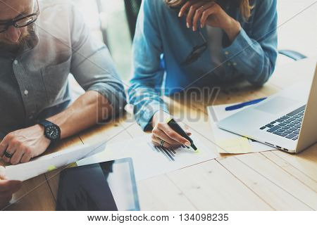 Coworkers team brainstorming process in modern loft.Project manager wearing glasses, woman makes notes marker.Creative business crew working with startup studio.Laptop wood table.Blurred, film effect