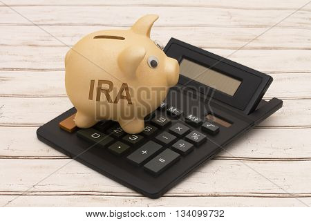 Saving for your retirement A golden piggy bank and calculator on a wood background with text IRA