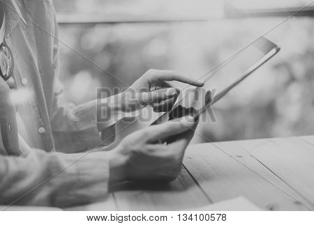 Work process modern Loft.Hipster working wood table with new freelance business startup.Marketing Department Research Process.Touching Screen Digital Tablet.Horizontal.Black White.Blurred background