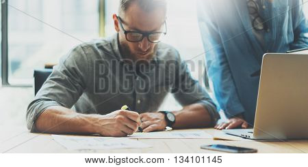Coworkers team.Analyzing stock report process modern design loft.Project manager wearing glasses, man makes notes marker.Creative business crew working new startup.Laptop wood table.Blurred, film effect