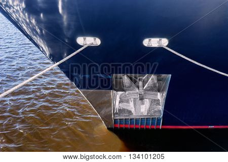 On-board the ship with the glare from the sun with an anchor on a red and white waterline ropes over water with waves