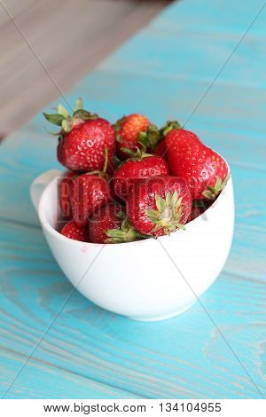 Strawberries in white cup on wooden blue desk. Stock photo.